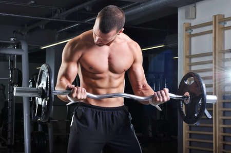 pectoral muscle: Handsome Muscular Male Model in a Standing Position With Perfect Body Doing Biceps Exercise Stock Photo