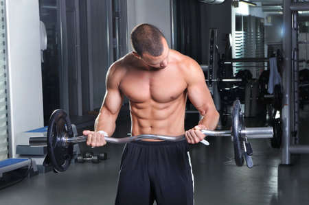 sixpack: Handsome Muscular Male Model in a Standing Position With Perfect Body Doing Biceps Exercise Stock Photo