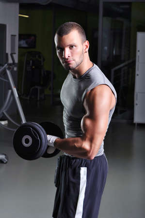 pectoral muscle: Handsome Muscular Male Model Doing Biceps Exercise with Dumbbells Stock Photo