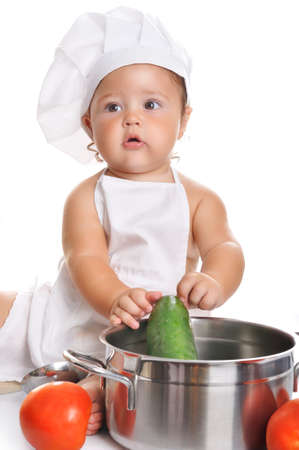 kitchen equipment: Funny adorable baby boy chef sitting and playing with kitchen equipment on a white background