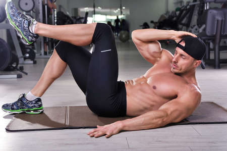 crunches: Handsome powerful athletic man performing crunches. Strong bodybuilder with perfect abs, chest and biceps.
