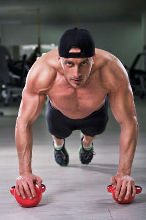push ups: Handsome powerful athletic man performing push ups with kettle bell. Strong bodybuilder with  perfect shoulders, biceps and triceps.