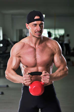 Handsome powerful athletic man doing biceps exercise with kettle bell. Strong bodybuilder with  perfect muscular abs, arms and chest.