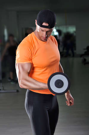 Handsome powerful athletic man performing biceps exercise with dumbbell. Strong bodybuilder with  perfect biceps and triceps.