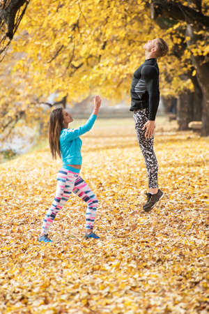 Beautiful young woman lifting up her man with a magic. Autumn environment.