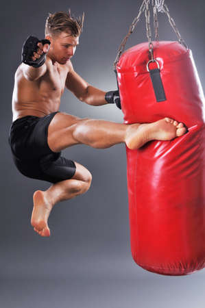 Muscular Fighter Practicing Some Kicks with Punching Bag. Boxing on Gray Background. The Concept of a Healthy Lifestyle Stock Photo