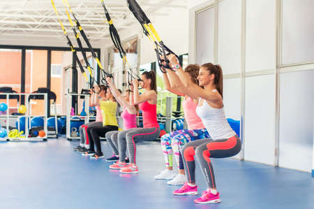 Group of beautiful young women working out on TRX  and smiling.
