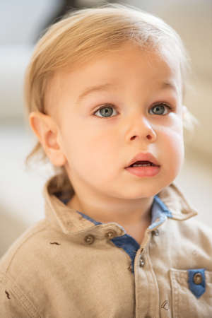 Portrait of little boy with blue eyes. Nicely dressed.