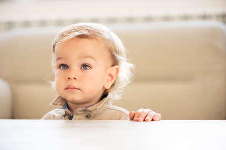 Retrato de niño pequeño con ojos azules mirando hacia arriba.