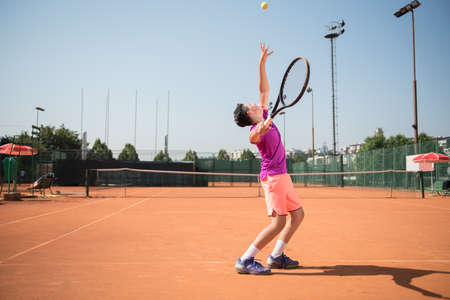 Young tennis player serving the ball Banque d'images