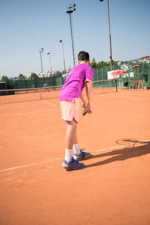 Young tennis player prepares for serving the ball