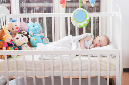 Beautiful baby boy laying down in his bed and sleeping 版權商用圖片 - 118455087