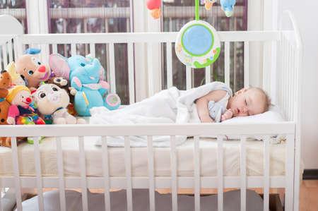 Schönes Baby, das sich in sein Bett legt und schläft Standard-Bild