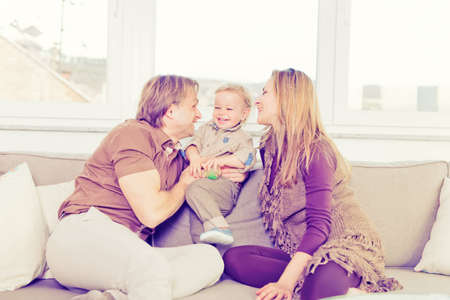 Portrait of happy family sitting on the sofa and playing. Stock Photo