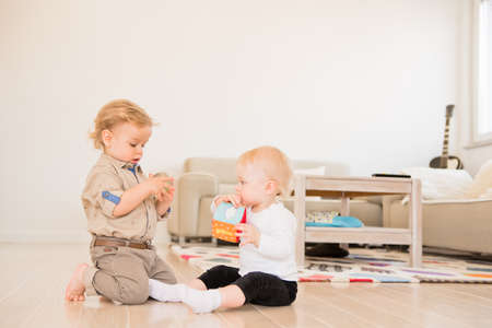 Cute little girl and boy playing with toys at home 스톡 콘텐츠