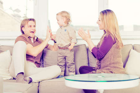 Portrait of happy family sitting on the sofa and playing. 写真素材