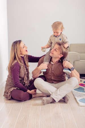 Happy family sitting on floor with their little baby. Family spending time at home with their son. 写真素材