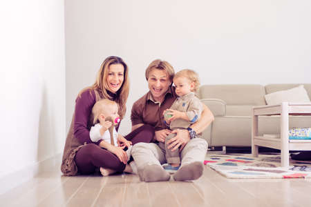 Happy family sitting on floor with their little babies Family spending time at home with their son and daughter.
