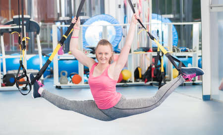Beautiful young woman doing exercise on TRX. Stockfoto
