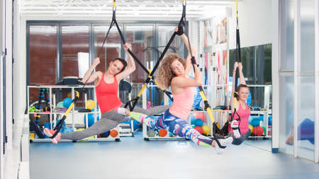 Group of beautiful young women doing exercise on TRX.