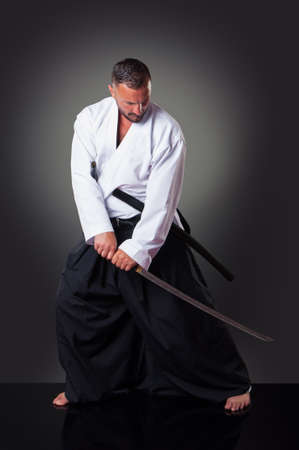 Handsome male karate player posing with the sword on the gray background. 스톡 콘텐츠