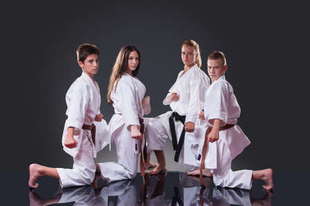 Group of young karate players posing on the gray background 版權商用圖片