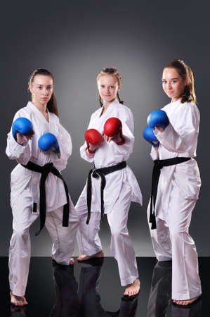 Group of beautiful young female karate players posing on the gray background