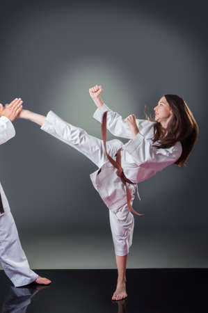 Beautiful young female karate player doing kick on the gray background Imagens