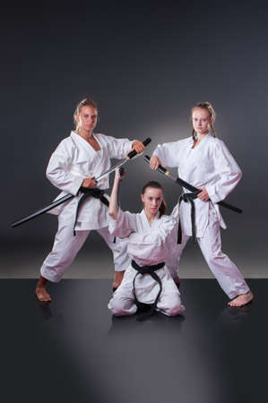 Beautiful young female karate players posing with sword on the
