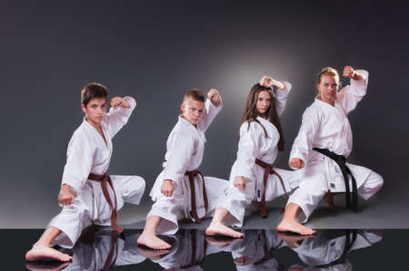 Group of young karate players doing kata on the gray background 版權商用圖片