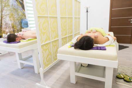 Junger Mann und Frau, die sich am Massagetisch niederlegen und Hijama-Behandlung machen. Standard-Bild