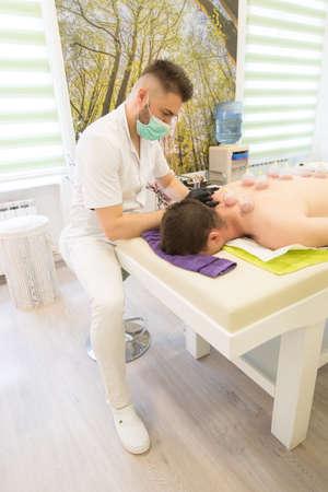 Junger Mann, der sich am Massagetisch niederlegt und eine Hijama-Behandlung macht