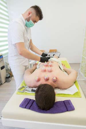 Junger Mann, der sich am Massagetisch niederlegt und eine Hijama-Behandlung macht. Standard-Bild