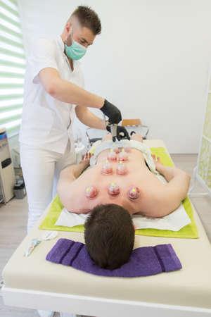 Jeune homme allongé à la table de massage et faisant un traitement hijama. Banque d'images