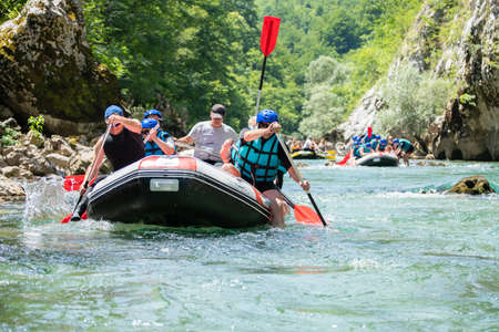 Rafting team goes down the river on the beautiful sunny day.