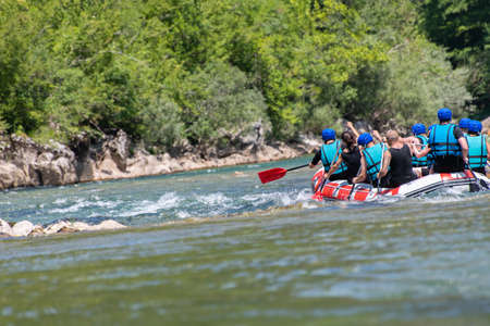 Rafting team goes down the river on the beautiful sunny day. Back view.