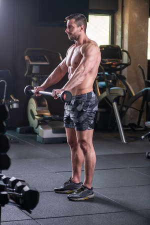 Sexy muscular man doing shoulders exercise with barbell Stock fotó