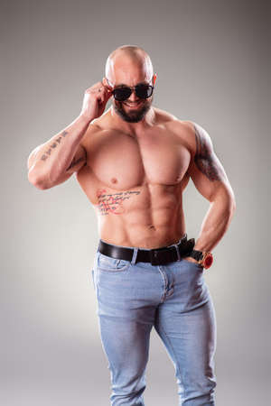 Sexy muscular bodybuider with sunglasses posing on the gray background