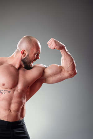 Sexy Muscular bodybuider posing on the gray background. Biceps contraction 版權商用圖片