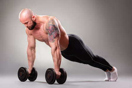 Sexy muscular bodybuider doing push ups with weights on the gray background