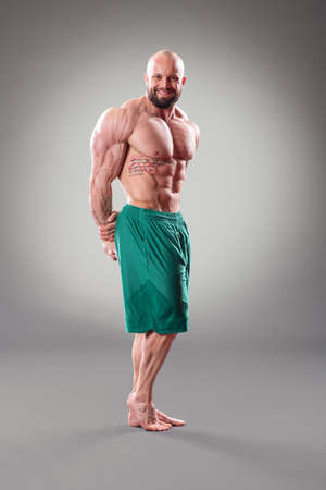 Sexy muscular bodybuider posing on the gray background Banque d'images