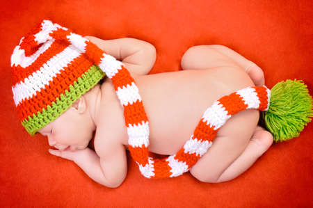Beautiful newborn baby boy with cute cap sleeping peacefully on the soft red blanket