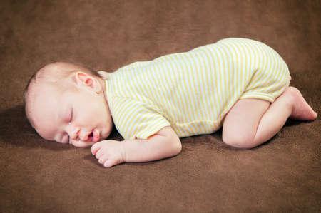 Beautiful newborn baby boy sleeping peacefully on the soft brown blanket Foto de archivo