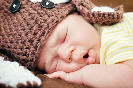 Beautiful newborn baby boy with cute cap sleeping peacefully on the soft brown blanket Foto de archivo