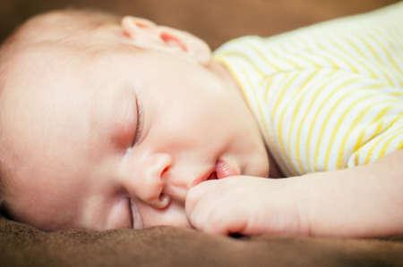 Beautiful newborn baby boy sleeping peacefully on the soft brown blanket