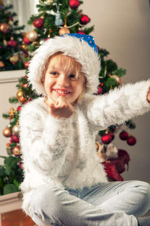 Beautiful little girl with santa claus hat sitting beside christmass tree. Thumb up