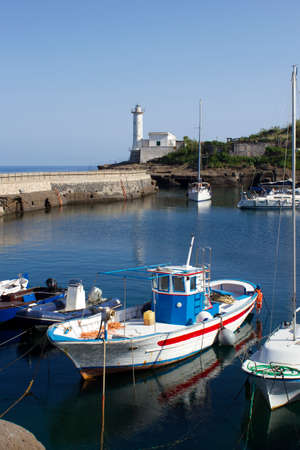 fishing boat in ventotene harbor and lighthouse