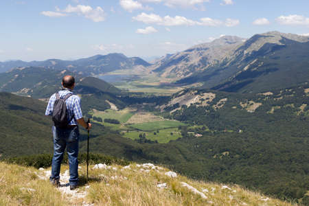 hiker in mountain landscape valley and lake