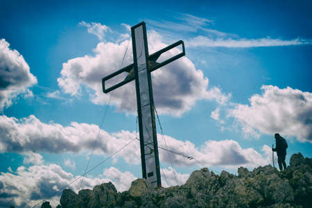 hiker on mountain and Christian cross Stock Photo