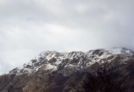 peaks of snow-capped mountains with bad weather